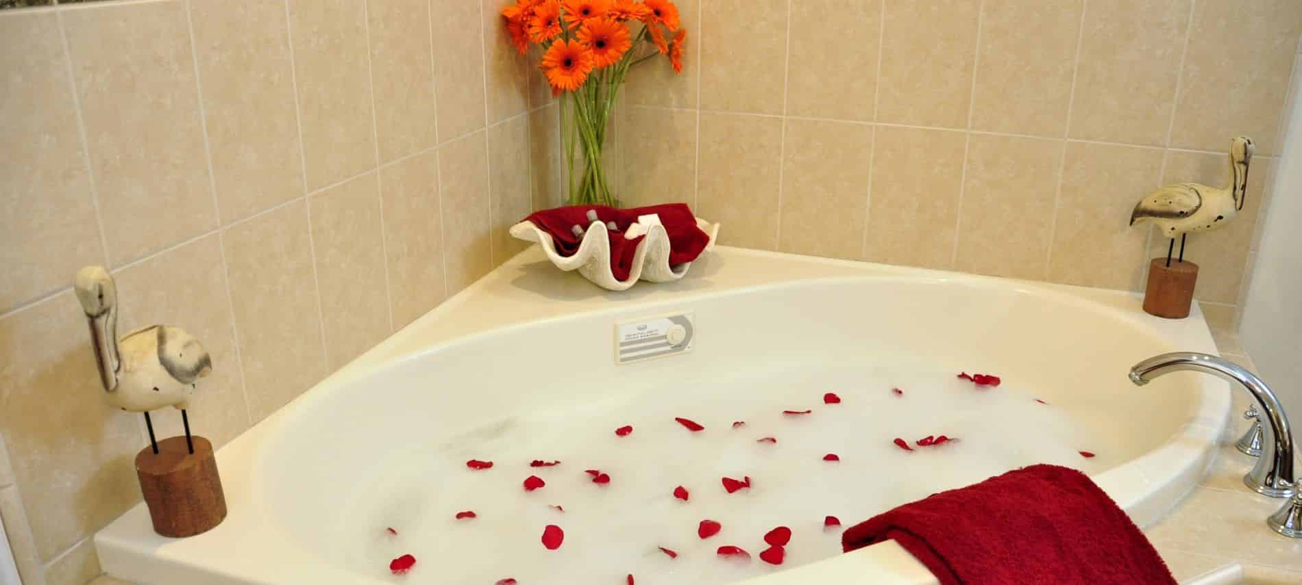 San Miguel guest bath corner tub with tiled walls and steps topped with red rose petals