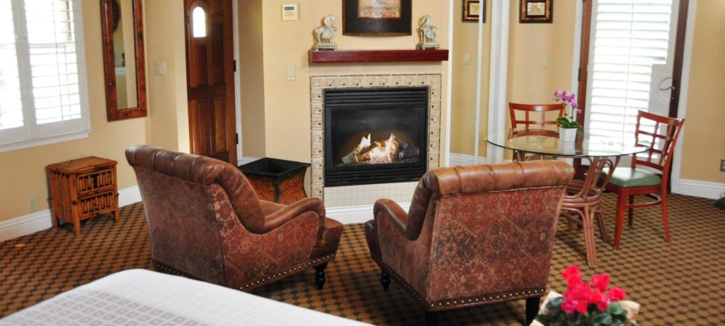 Spacious Santa Rosa guest room with fireplace, two leather chairs, and carpeting