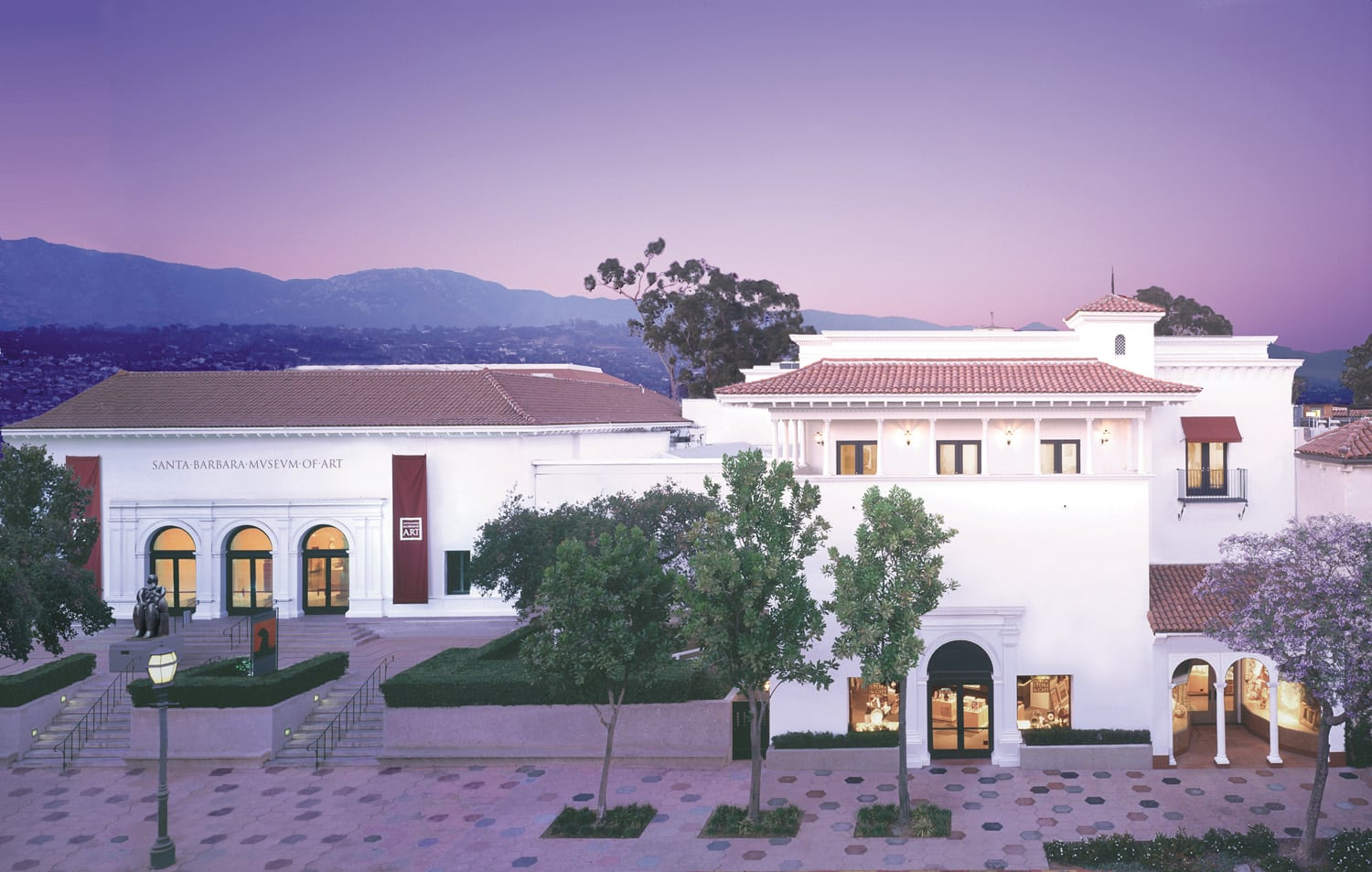 Exterior of Santa Barbara Museum of Art amidst purple skies and distant mountains