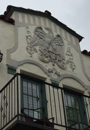 Close up view of The Eagle Inn's stucco building with engraved Eagle and balcony with black metal railing