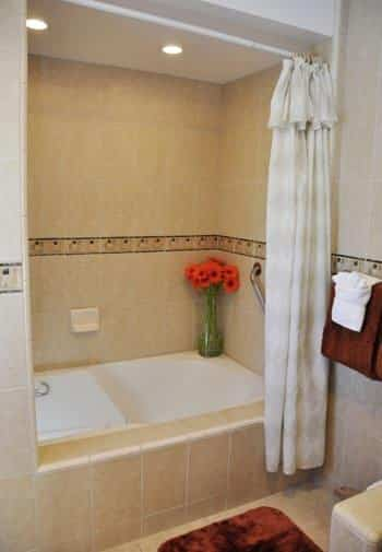 Anacapa guest bath with white tub surrounded by tiled walls and white shower curtain