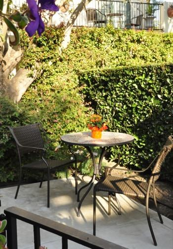 Anacapa guest patio with round table and two chairs surrounded by green shrubs