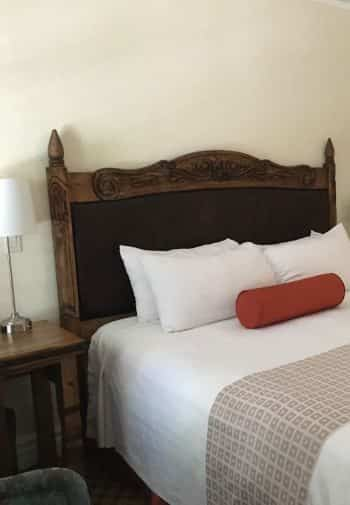 King guest room with wood and leather headboard and white linens