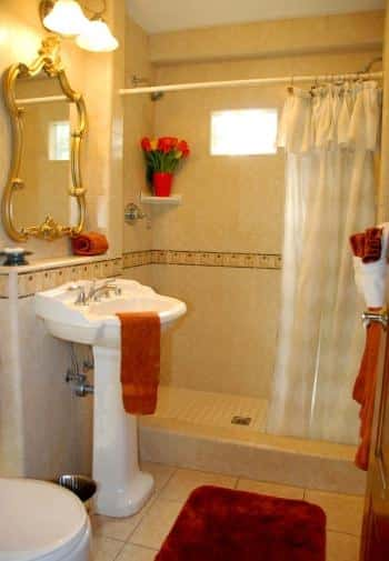 King bathroom with white pedestal sink and tiled shower