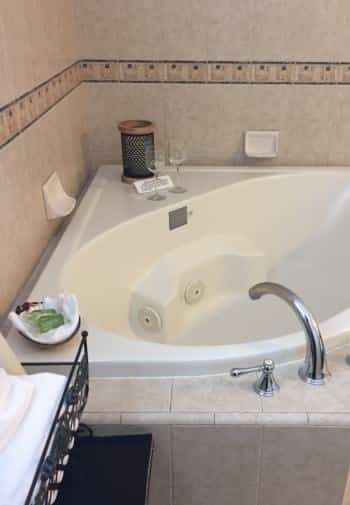 Deluxe king guest room with whirlpool tub surrounded by tile