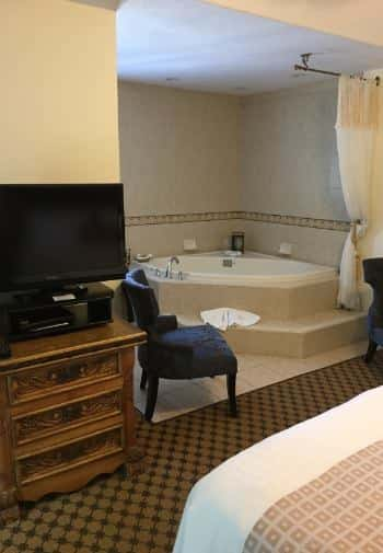 Deluxe king guest room with TV on wooden dresser and whirlpool tub