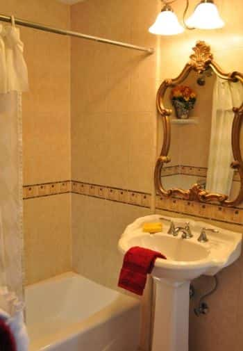 Deluxe King balcony bathroom with white pedestal sink, white tub surrounded by tile, and vintage mirror