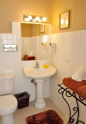 Queen balcony guest room bathroom with white pedestal sink and white tile on walls
