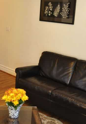 San Clemente guest room with leather couch and coffee table with yellow flowers