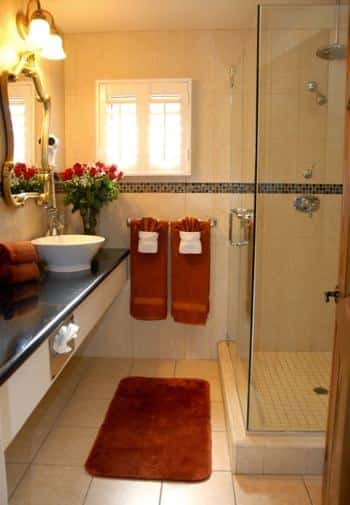 San Nicolas guest bath, small window, long black vanity top with white vessel bowl sink and tiled shower with glass door