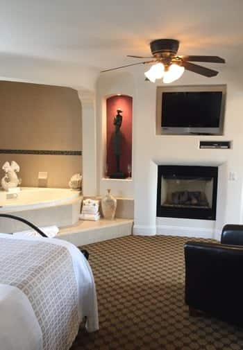 San Nicolas guest room with white walls, semi-enclosed corner tub, red niche with sculpture and light, fireplace and TV