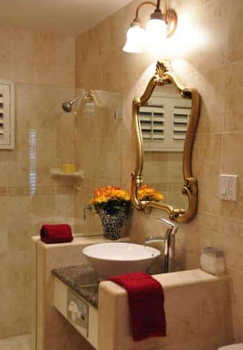 Santa Barbara guest bath with tiled walls and shower, glass shower door, white vessel bowl sink and gold mirror
