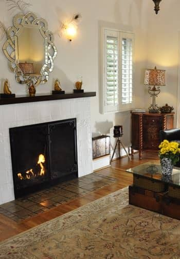 Santa Barbara guest room with shuttered window, fireplace with tile surround and black mantel, silver mirror, and wood floor