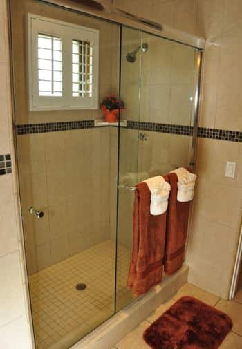 Santa Catalina guest bath with tiled walk-in shower, small window, and glass shower door