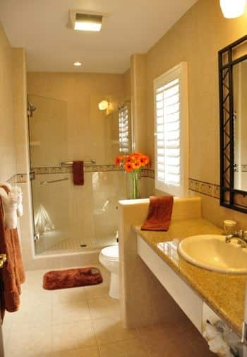 Santa Cruz guest bath with window, tiled shower with glass door, long vanity with sink and wall mirror