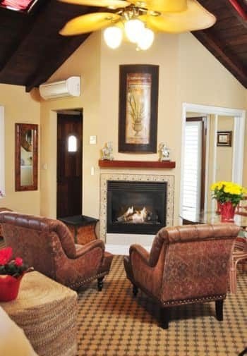 Santa Rosa guest room with vaulted wood ceilings, corner fireplace, two leather chairs, carpeting and ceiling fan