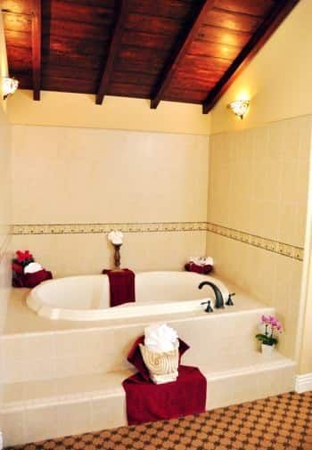 Santa Rosa guest bath with wood ceiling, and tub enclosed in tiled walls and steps
