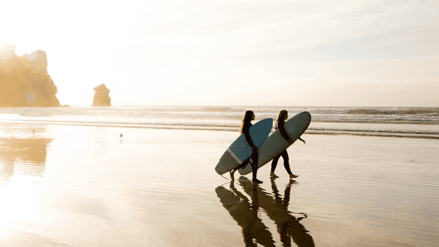 Two Surfers holding boards standing in water walking toward waves