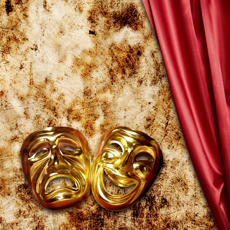 Gold sad and happy theater masks against a gold and red satin background